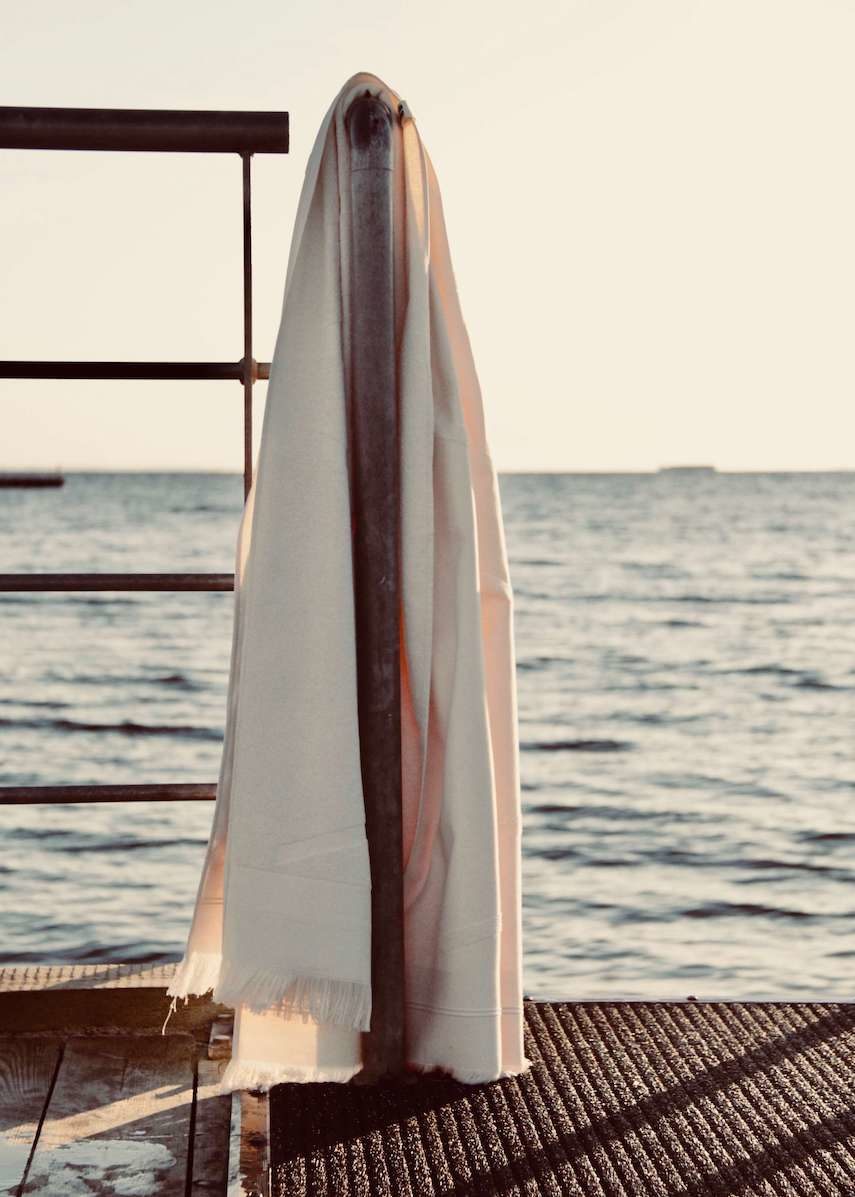 White WAY beach towel hanging on rail by the sea
