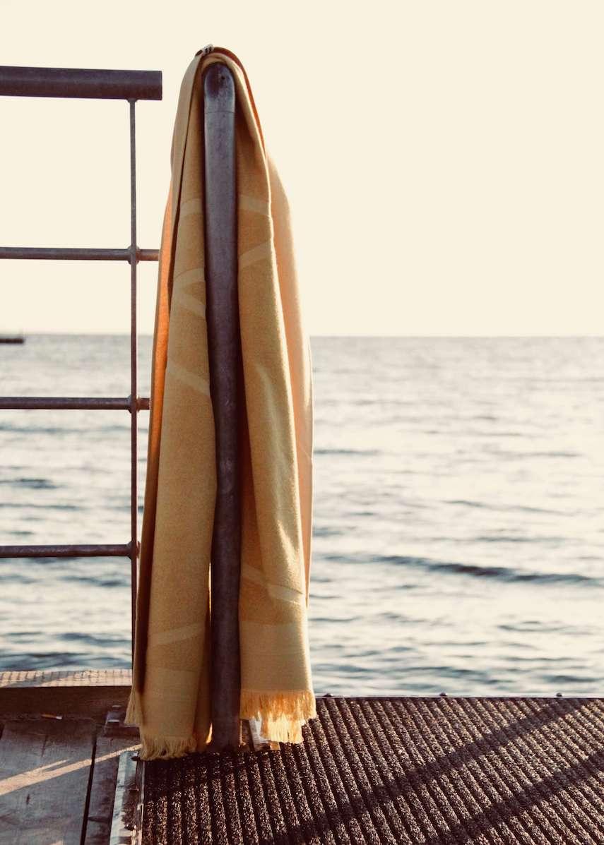Yellow WAY beach towel hanging on rail by the sea