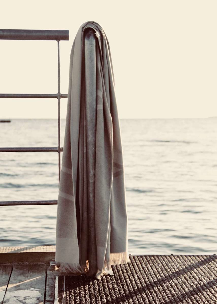 Grey WAY beach towel hanging on rail by the sea