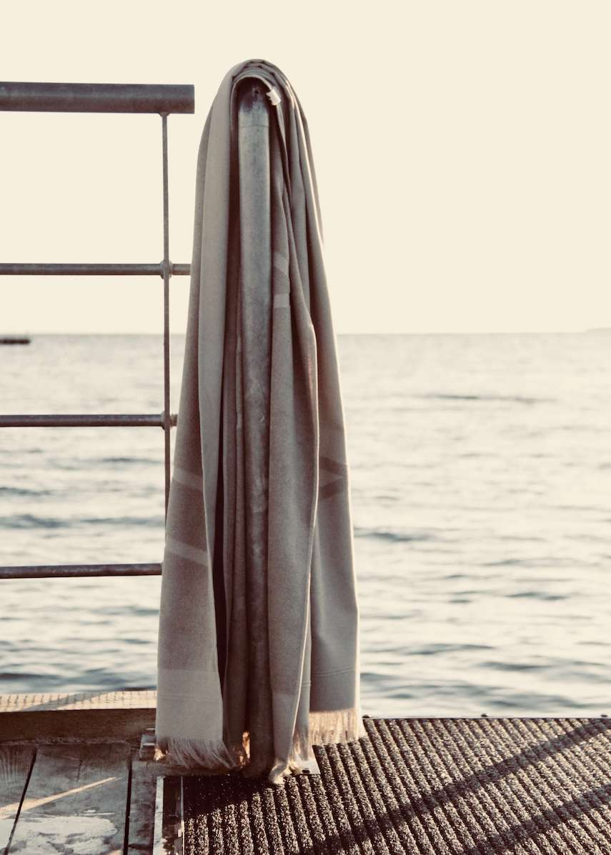 Grey WAY beach towel hanging on rail by the sea