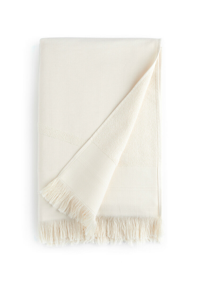 Folded white WAY beach towel with woven front and terry back and fringes