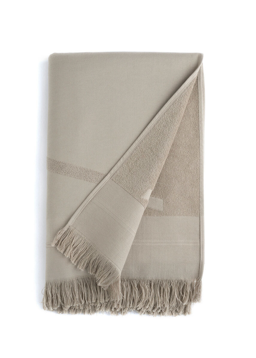 Folded grey WAY beach towel with woven front and terry back and fringes